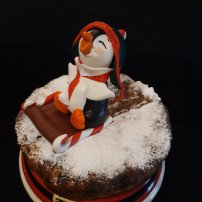 Christmas fruit cake decorated with a Penguin cake topper. Sugar paste modeling